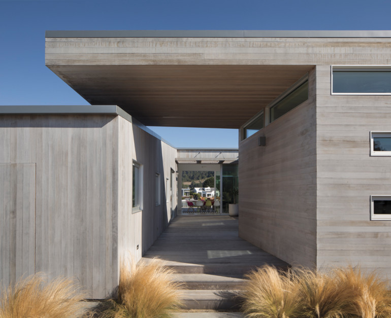 "A house with a cantilevered roof that forms a breezeway canopy is architect Cass Calder Smith's version of a bleached wood beach ""shack"" for a surfing family."